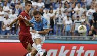 Penyerang Lazio, Ciro Immobile menendang bola ke arah gawang AS Roma pada pertandingan Serie A Liga Italia di stadion Olimpico (1/9/2019). Lazio dan Roma bermain imbang 1-1. (AP Photo/Alessandra Tarantino)