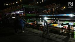 Pedagang melayani pembeli saat menjajakan dagangannya di atas perahu di Alun-Alun Sungai Kapuas, Pontianak, Kalimantan Barat, Kamis (12/4). Akibat dilarang, para pedagang ini memilih berdagang di atas perahu. (Liputan6.com/Johan Tallo)