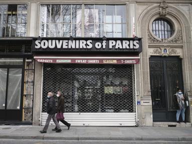 Orang-orang berjalan di depan toko suvenir yang tutup di Paris (22/3/2021).  Penduduk Paris dan beberapa wilayah Prancis lainnya menghabiskan akhir pekan pertama mereka di bawah penguncian terbatas selama sebulan.  (AP Photo/Lewis Joly)