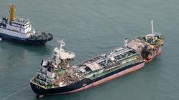 Pemandangan udara dari helikopter Jiji Press menunjukkan sebuah kapal tanker minyak ditarik setelah bertabrakan dengan jembatan yang menghubungkan ke Bandara Internasional Kansai di kota Izumisano, prefektur Osaka (5/9). (AFP Photo/Jiji Press)