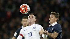 Pemain Inggris Wayne Rooney (kiri)  berebut bola dengan pemain Prancis Lucas Digne Pada laga Persahabatan di Stadion Wembley, London, Rabu(18/11/2015) dini hari WIB. (AFP Photo/Adrian Dennis)