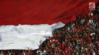 Suporter Timnas Indonesia membentangkan bendera raksasa saat menyaksikan laga persahabatan antara Indonesia melawan Fiji di Stadion Patriot Candrabhaga, Bekasi, Sabtu (9/2). Laga berakhir imbang 0-0. (Liputan6.com/Helmi Fithriansyah)