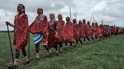 Sejumlah suku Masaai berjalan bersiap mengikuti kompetisi Olimpiade Maasai 2018 di Kimana, dekat perbatasan Kenya dengan Tanzania (15/12). Olimpiade Maasai  sudah diadakan setiap dua tahun sejak 2012. (AFP Photo/Yasuyoshi Chiba)
