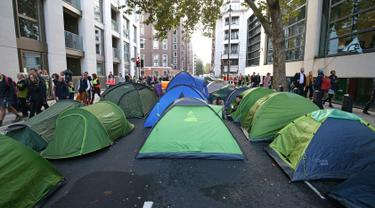 Aktivis iklim mendirikan tenda saat berkemah di jalan utama Westminster, London, Inggris, Selasa (8/10/2019). Aksi yang bertujuan mendesak pemerintah mengekang emisi karbon tersebut bagian dari gerakan Pemberontakan Kepunahan. (Jonathan Brady/PA via AP)