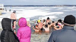 Orang-orang menyaksikan penggemar renang es di Danau Zalew Zegrzynski di Nieporet, Polandia, Minggu (25/2). Gelombang dingin sedang melanda Polandia. (AP Photo/Alik Keplicz)