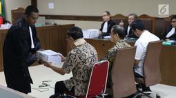 Terdakwa suap anggota DPRD Kalteng, Edy Saputra Suradja (kiri) menerima surat tuntutan dari JPU KPK usai dibacakan pada sidang di Pengadilan Tipikor, Jakarta, (27/2). Edy Saputra Suradja dituntut 2 tahun 6 bulan penjara. (Liputan6.com/Helmi Fithriansyah)
