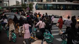 Orang-orang mencoba melewati lalu lintas saat mereka bepergian dengan sepeda selama jam sibuk di Beijing, China pada 14 Oktober 2020. (Photo by NICOLAS ASFOURI / AFP)