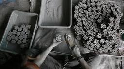 Pekerja memasukan bubuk mesiu ketabung kertas untuk membuat petasan yang digunakan dalam festival Diwali di Ahmadabad, India (27/9). Menjelang perayaan Diwali, sejumlah produsen petasan di India dibajiri pesanan. (AP Photo/Ajit Solanki)