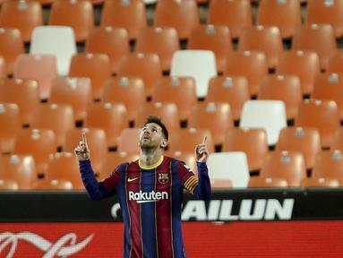 Penyerang Barcelona, Lionel Messi berselebrasi usai mencetak gol ke gawang Valencia pada pertandingan La Liga Spanyol di stadion Mestalla, Senin (3/5/2021). Messi mencetak dua gol dan mengantar Barcelona menang tipis atas Valencia 3-2. (AP Photo/Alberto Saiz)