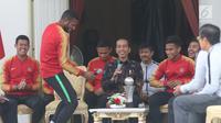 Presiden Joko Widodo (Jokowi) tertawa melihat aksi Marinus Wanewar saat menerima pemain Timnas U-22 Indonesia yang baru saja menjuarai Piala AFF U-22 2019, di beranda belakang Istana Merdeka, Jakarta, Kamis (28/2). (Liputan6.com/Angga Yuniar)