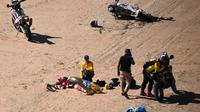 Pembalap asal Portugal, Paulo Goncalves tengah mendapatkan pertolongan dari tim medis saat mengalami kecelakaan di etape ketujuh Reli Dakar, Minggu (12/1/2020). Nyawanya tidak tertolong meski sempat dilarikan ke rumah sakit dengan helikopter. (Frank FIFE/