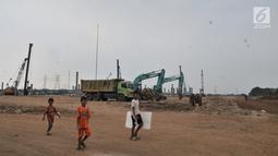 Anak-anak saat bermain di area proyek pembangunan Stadion BMW, Jakarta, Rabu (10/7/2019). Saat ini progres pembangunan stadion untuk markas Persija tersebut telah mencapai pemasangan tiang pancang dan PT Jakpro menargetkan proyek selesai pada 2021. (merdeka.com/Iqbal S. Nugroho)