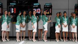 Sejumlah grid girl atau gadis pendamping bersiap untuk mendampingi para pembalap sebelum dimulainya Grand Prix Formula 1 Malaysia di Sepang (1/10). Para gadis payung ini terlihat seksi dengan baju ketat yang dikenakannnya. (AFP Photo/Manan Vatsyayana)
