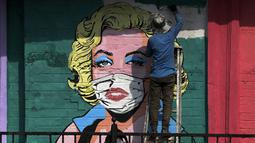 Seniman melukis mural untuk menyebarkan kesadaran akan pencegahan virus corona di Mumbai, India (26/3/2021). Kementerian Kesehatan melaporkan 43.846 kasus baru dalam 24 jam terakhir, peningkatan satu hari terburuk sejak pertengahan November. (AP Photo/Rajanish Kakade)