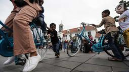 Pengunjung bersepeda mengelilingi Kawasan Kota Tua, Jakarta, Selasa (26/12). Libur Natal dimanfaatkan warga untuk berwisata di sejumlah lokasi seperti Museum Fatahillah, Kebun Binatang Ragunan, kawasan Ancol serta Monas. (Liputan6.com/Faizal Fanani)