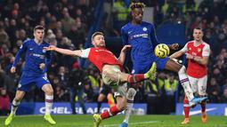 Striker Chelsea, Tammy Abraham, berebut bola dengan bek Arsenal, Shkodran Mustafi, pada laga Premier League pekan ke-24 di Stamford Bridge, London, Rabu (22/1). Arsenal tahan imbang Chelsea 2-2. (AFP/Ben Stansall)