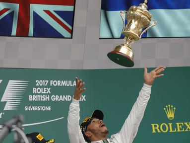 Pebalap Mercedes, Lewis Hamilton, melempar trofi usai menjuarai F1 GP Inggris di Sirkuit Silverstone, Minggu (16/7/2017). Pebalap 32 tahun asal Inggris itu melahap 51 lap dengan catatan waktu 1 jam 21 menit 27,430 detik. (EPA/Valdrin Xhemaj)
