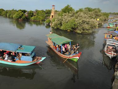 Perahu wisata melintasi kerumunan wisatawan yang berjalan di atas Jembatan Cinta di Wisata Mangrove, Tarumajaya, Bekasi, Minggu (30/12). Wisata tersebut berbatasan langsung dengan kawasan Marunda Jakarta Utara. (merdeka.com/Arie Basuki)