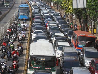 Pengendara memasuki jalur bus Transjakarta di Jalan Mampang, Jakarta, Senin (13/6). Polisi akan memberikan surat tilang slip biru dengan denda tilang sebesar Rp500.000 bagi pengendara yang memasuki jalur Transjakarta. (Liputan6.com/Gempur M Surya)