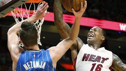 Pemain Miami Heat, James Johnson #16 melakukan blok atas tembakan pemain Orlando Magic, Mario Hezonja #8  pada laga NBA preseason basketball game, di Miami (19/10/2016) WIB. (AP/Wilfredo Lee)