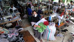 Warga menyelesaikan pembuatan baju di sebuah usaha konveksi milik Enca di Desa Curug, Bogor, Jawa Barat, Kamis (4/3/2021). Kini produksinya rata-rata 1500 setel pakaian per minggu dengan omzet sebulan lebih dari Rp 150 juta dan mampu mempekerjakan 17 orang warga desa. (merdeka.com/Arie Basuki)