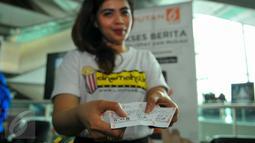 Seorang wanita memperlihatkan tiket nonton bareng Cinemaholic di Blitz Megaplek, Jakarta, Sabtu (21/5/2016). Cinemaholic dan Primagama gelar nonton bareng film X-Men Apocalypse. (Liputan6.com/Yoppy Renato)