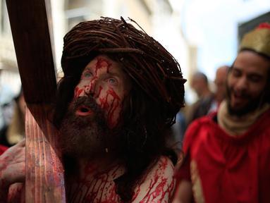 Seorang aktor berpakaian seperti Yesus Kristus memanggul salib saat melakukan prosesi Jalan Salib menyusuri Via Dolorosa menuju Gereja Makam Suci di Kota Tua Yerusalem, Jumat (19/4). Via Dolorosa diyakini sebagai jalan yang dilalui Yesus dalam proses penyaliban. (AP Photo/Ariel Schalit)