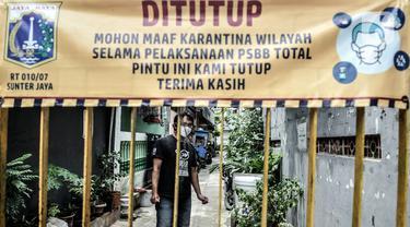 Warga berada di balik pagar salah satu wilayah zona merah COVID-19 di RW 07 Kelurahan Sunter Jaya, Jakarta, Rabu (10/2/2021). Pemprov DKI Jakarta mencatat wilayah zona merah COVID-19 melonjak jadi 82 rukun warga (RW). (merdeka.com/Iqbal S. Nugroho)