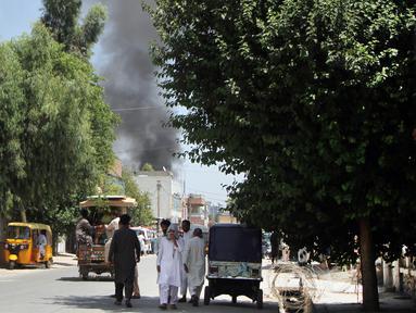 Kepulan asap membumbung dari sebuah gedung pemerintahan Afghanistan setelah bom bunuh diri dan serangan kelompok bersenjata di Jalalabad, Selasa (31/7). Setidaknya 15 orang tewas dan puluhan orang lainnya mengalami luka-luka akibat insiden ini. (AP Photo)