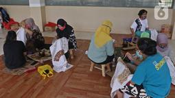 Perajin menyelesaikan salah satu tahapan produksi batik Marunda di Rusunawa Marunda, Jakarta, Selasa (14/7/2020). Pembuatan batik Marunda dimulai dengan melukis pola, mencelup, hingga memberikan warna. (Liputan6.com/Herman Zakharia)