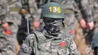 Pemain Tottenham Hotspur, Son Heung-min, berseragam militer lengkap dengan senjata saat mengikuti wajib militer di Korsel, (6/5/2020). Penundaan Premier League karena virus corona dimanfaatkan Son Heung-min untuk mengikuti program wajib militer. (AFP/STR)