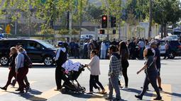 Para wali murid menunggu anak mereka di seberang lokasi penembakan di sekolah menengah Salvador Castro, Los Angeles, Kamis (1/2). Kepolisian mengatakan bahwa tersangka penembak dan senjata yang dimiliki sudah diamankan oleh polisi. (AP/Damian Dovarganes)