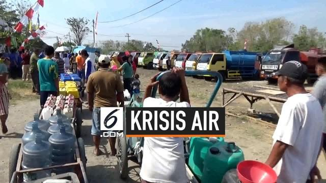 Warga di Gresik, Jawa Timur antri panjang demi mendapatkan bantuan air bersih yang diberikan oleh sebuah perusahaan air minum.