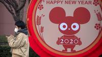 Seorang perempuan mengenakan masker berdiri dekat layar untuk perayaan Imlek Tahun Tikus Logam di Beijing, 22 Januari 2020. Otoritas kesehatan China mendesak orang-orang menghindari keramaian dan pertemuan publik di Wuhan, kota yang menjadi pusat penyebaran wabah virus corona. (AP/Mark Schiefelbein)
