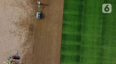 Pekerja melakukan proses perataan tanah untuk pemasangan rumput hybrid di area lapangan latih Jakarta International Stadium, Jumat (23/10/2020). Sebanyak dua lapangan latih JIS mulai dilakukan pemasangan rumput hybrid dan ditarget selesai pada Desember 2020. (Liputan6.com/Helmi Fithriansyah)