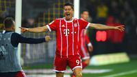 Robert Lewandowski melakukan selebrasi usai mencetak gol ke gawang Borussia Dortmund pada pertandingan Bundesliga Jerman di Dortmund, (4/11). Munchen menang telak 3-1 atas Dortmund. (AFP Photo/Patrik Stollarz)