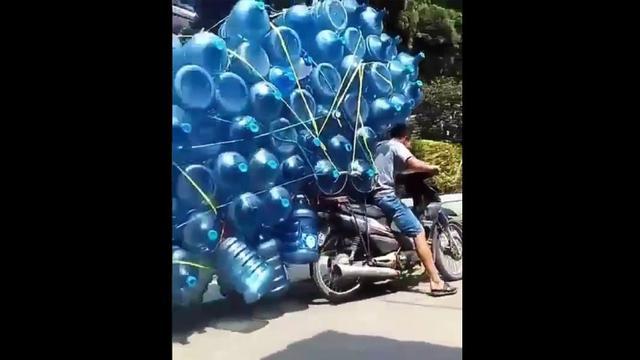 Pengendara sepeda motor membawa galon