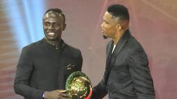 Mantan penyerang Kamerun Samuel Eto'o (kanan) memberi selamat kepada penyerang Senegal Sadio Mane (kiri) setelah memenangkan penghargaan Pemain Terbaik Afrika 2019 selama CAF Awards di kota wisata Mesir, Hurghada (7/1/2020). (AFP/Khaled Desouki)