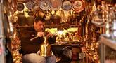 Pedagang barang antik Saadoun Mansouri bekerja di tokonya di Baghdad, Irak, Rabu (20/3). (AP Photo/Hadi Mizan)