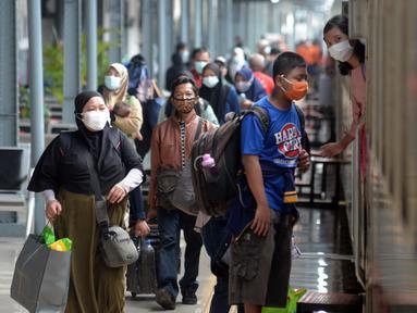 Penumpang menaiki kereta api Bangunkarta jurusan Jakarta-Jombang di Stasiun Senen, Jakarta, Selasa (18/5/2021). Berakhirnya larangan mudik pada 17 Mei 2021, Stasiun Senen ramai oleh pemudik susulan yang hendak berangkat ke kampung halaman di Jawa Tengah dan Jawa Timur. (merdeka.com/Imam Buhori)