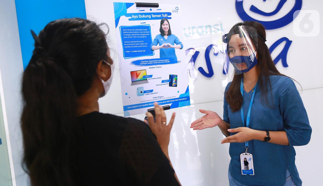 """Frontliner kenakan masker melayani nasabah di kantor Asuransi Astra Tendean, di Jakarta, Selasa (1/9/2020). Asuransi Astra ajak warganet turut serta dalam kampanye sosial """"Teman Tuli Asuransi Astra"""" dengan mengunggah foto menggunakan pose bahasa isyarat """"cinta"""" ke Instagram. (Liputan6.com/HO/Eko)"""