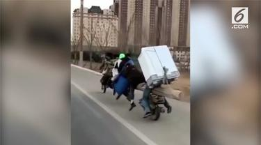 Sepeda motor berbentuk tak biasa mengangkut 7 anggota keluarga dan sebuah lemari es. Kendaraan itu melaju di jalanan Kota Chong Qing.