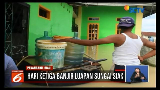 Hari ketiga banjir di Pekanbaru, Riau, warga Perumahan Witayu, Kecamatan Rumbai, masih bertahan di rumah. Meski demikian, mereka mulai kekurangan air bersih.