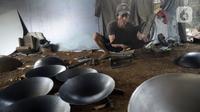 Perajin menyelesaikan pembuatan wajan yang terbuat dari pelat besi di Desa Cibadak, Tanah Sareal, Kabupaten Bogor, Jawa Barat, Rabu (5/8/2020). Pemerintah akan memberi bantuan Rp 2,4 juta dan kredit bunga rendah kepada UMKM untuk membantu pemulihan ekonomi nasional. (merdeka.com/Dwi Narwoko)