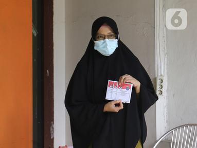 Warga yang diduga terpapar COVID-19 menunjukkan surat suara di kawasan Depok, Jawa Barat, Rabu (9/12/2020). Petugas KPPS melakukan jemput bola atau mengambil suara dari warga yang diduga terpapar COVID-19 atau sedang menjalani isolasi mandiri di Pilkada Depok 2020. (Liputan6.com/Herman Zakharia)
