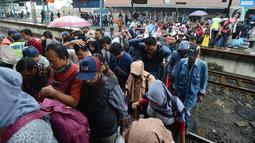 Penumpang kereta commuter line menyeberang rel kereta di Stasiun Manggarai, Jakarta, Selasa (22/1). PT. Kereta Commuter Indonesia (KCI) menutup jalur 10 di Stasiun Manggarai guna mempercepat revitalisasi yang sedang dilakukan. (Merdeka.com/Imam Buhori)