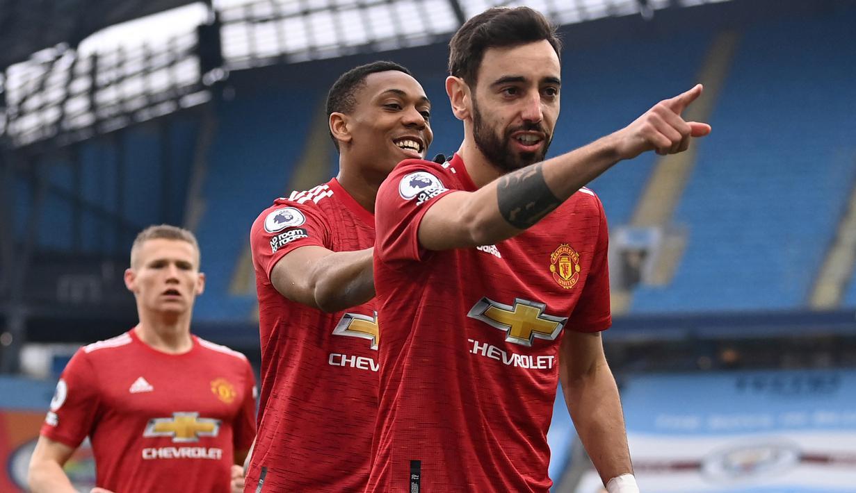Gelandang Manchester United, Bruno Fernandes (depan) melakukan selebrasi usai mencetak gol pertama timnya ke gawang Manchester City melalui eksekusi penalti dalam laga lanjutan Liga Inggris 2020/21 di Etihad Stadium, Minggu (7/3/2021). MU menang 2-0 atas Mancity. (AFP/Laurence Griffiths/Pool)