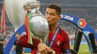 Cristiano Ronaldo menciumi Piala Eropa 2016 usai memenangkan laga melawan Prancis di Stade de France, Senin (11/7). Portugal menang dengan skor tipis 1-0. (REUTERS)