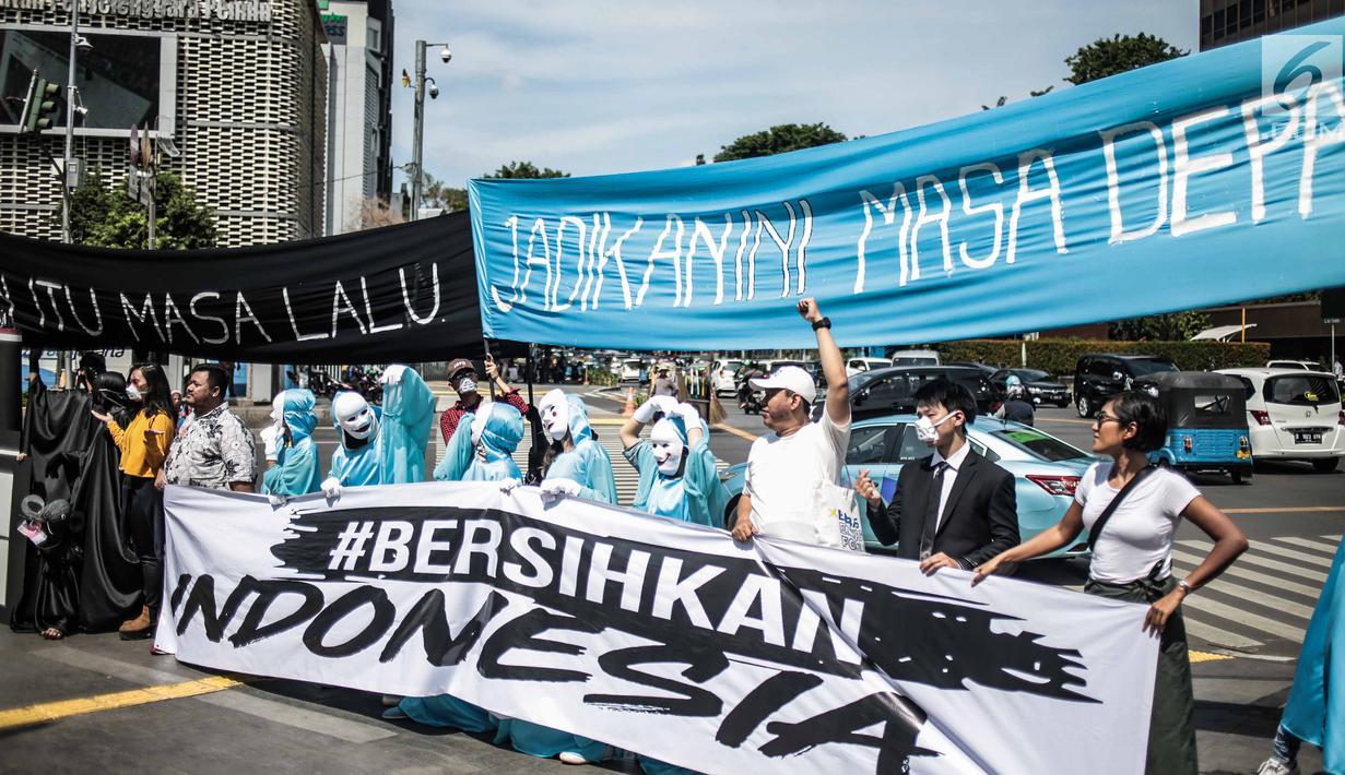 Sejumlah massa aksi yang tergabung dalam gerakan masyarakat non partisan #BersihkanIndonesia gelar aksi teatrikal di lintasan penyeberangan orang atau Pelican crossing di Jakarta, Kamis (20/12). (Liputan6.com/Faizal Fanani)