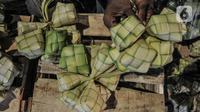 Aktivitas pedagang saat membuat bungkus atau tali ketupat di Pasar Klender, Jakarta Timur, Selasa (11/5/2021) malam. Biasanya empat hari menjelang Lebaran pedagang ketupat musiman tersebut mulai bermunculan menjajakan bahan baku makanan khas Idul Fitri ini. (merdeka.com/Iqbal S Nugroho)